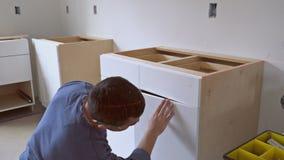 Arbeider die keukenkast installeren stock video