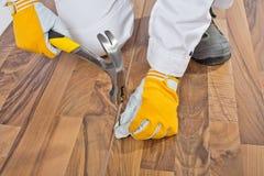 Arbeider die met een hamer houten vloer wordt genageld Stock Foto's