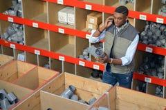 Arbeider die met klembord smartphone uitnodigen bij pakhuis stock foto
