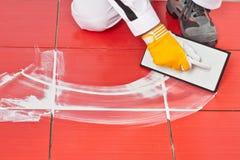 Arbeider die met rubbertroffel pleistertegel toepast Stock Afbeelding