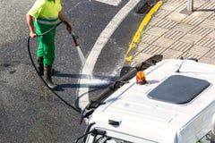 Arbeider die met water de weg en straatstoep schoonmaken stock fotografie