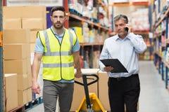 Arbeider die met zijn manager over de telefoon lopen stock fotografie