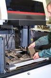 Arbeider die metaaldetail in cnc industriële machine onderzoeken stock afbeelding