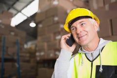 Arbeider die mobiele telefoon in pakhuis met behulp van royalty-vrije stock afbeeldingen