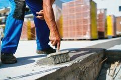 arbeider die op bouwwerf dichtingsproduct voor het waterdicht maken van beton op bouwwerf leggen stock afbeelding