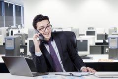 Arbeider die op cellphone in bureauruimte spreken Stock Foto's