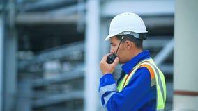 Arbeider die op de radio, industriële scène op achtergrond spreken stock video