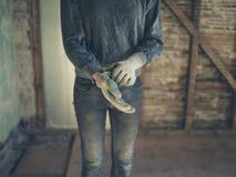 Arbeider die op handschoenen in zolder zetten stock afbeelding
