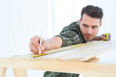 Arbeider die op houten plank merken Stock Foto