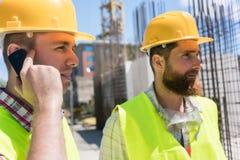Arbeider die op mobiele telefoon tijdens het werk aangaande een bouwwerf spreken stock foto