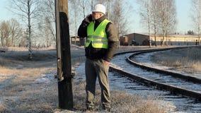 Arbeider die op smartphone bij de pool met hoog voltage dichtbij spoorweg in de winter spreken stock footage