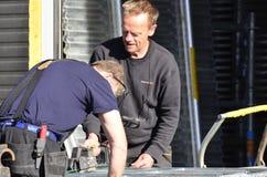 Arbeider die op werf met vrachtwagenlift het werk voorbereiden stock foto's