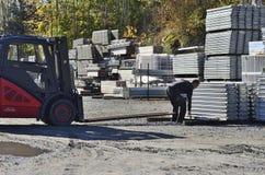 Arbeider die op werf met vrachtwagenlift het werk voorbereiden stock afbeelding