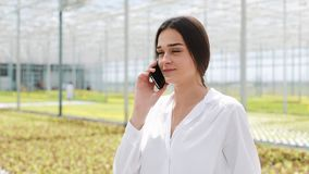 Arbeider die in serre mobiel gebruiken en het spreken op smartphone lopen Landbouwingenieur die in serre werken stock video