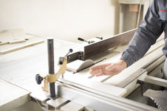 Arbeider die silicone glueCloseup proces van timmermansarbeider gebruiken met cirkelzaagmachine bij houten straal dwarsknipsel ti Stock Afbeelding