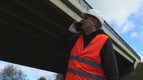Arbeider die smartphone gebruiken bij brug stock video