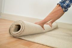 Arbeider die tapijt op vloer vouwen stock foto's