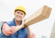 Arbeider die terwijl het Dragen van Houten Plank glimlachen stock foto