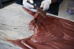 Arbeider die uit chocolade op een lijst met spatels uitspreiden stock foto's