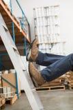 Arbeider die van ladder in pakhuis vallen Royalty-vrije Stock Foto's