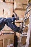 Arbeider die van ladder in pakhuis vallen Stock Afbeeldingen