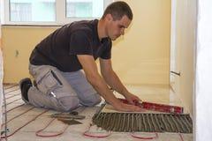 Arbeider die vloertegels installeren Keramische tegels en hulpmiddelen voor tegelzetter Stock Foto
