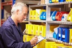 Arbeider die Voorraadniveaus in Opslagzaal controleren Stock Foto's