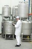 Arbeider die voorraden in levensmiddelenpakhuis controleert royalty-vrije stock afbeeldingen