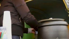 Arbeider die warme soep gieten aan voerdaklozen en armen, vrijwilligersprogramma stock footage