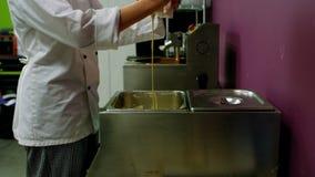 Arbeider die witte smeltende chocolade in container gieten stock video