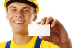 Arbeider die zijn adreskaartje en glimlach toont stock afbeeldingen