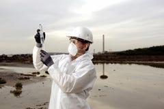 Arbeider in een beschermend kostuum dat verontreiniging onderzoekt Stock Foto's