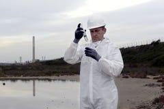 Arbeider in een beschermend kostuum dat verontreiniging onderzoekt Stock Afbeelding