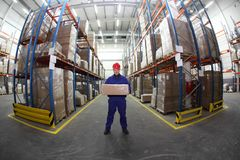 Arbeider in eenvormig met doos in het pakhuis stock foto