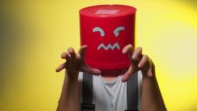 Arbeider in eenvormig met rode emmer op zijn boos hoofd stock footage