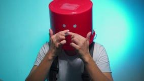 Arbeider in eenvormig met rode emmer op zijn droevig hoofd stock video