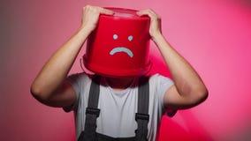 Arbeider in eenvormig met rode emmer op zijn droevig hoofd stock videobeelden