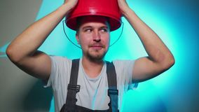 Arbeider in eenvormig met rode emmer op zijn droevig hoofd stock footage