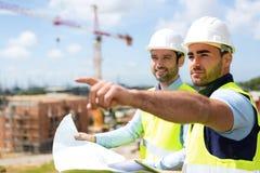 Arbeider en architect die op sommige details op een bouw letten Stock Afbeeldingen