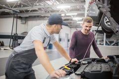 Arbeider en eigenaar van autotribune bij geopend voorlichaam van voertuig De gebaarde mens bekijkt het De arbeider leunt aan auto royalty-vrije stock afbeeldingen