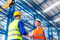 Arbeider en klant die overeenkomst in fabriek hebben Stock Foto's