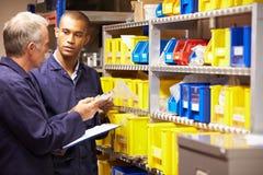 Arbeider en Leerling die Voorraadniveaus in Opslagzaal controleren Stock Fotografie