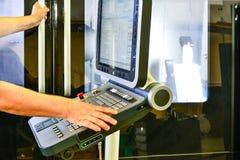 Arbeider, exploitant van het controlebord van het programma van verrichting die van een high-precision CNC machinaal bewerkend ce royalty-vrije stock afbeelding