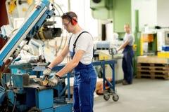 Arbeider in fabriek stock afbeelding