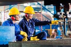 Arbeider in fabriek bij industriële machine om metaal te snijden Stock Foto's