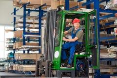 Arbeider in fabriek in liftvrachtwagen Stock Foto's
