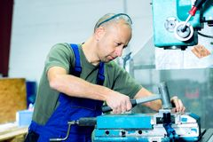 Arbeider in fabriek op de machine Stock Afbeelding