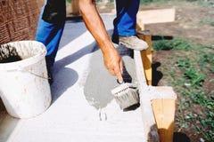 arbeider gebruikend borstel en inleiding voor het hydroisolating en waterdicht makend huis royalty-vrije stock foto's