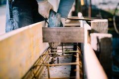 Arbeider gebruikend een hulpmiddel van de boormacht op bouwwerf en creërend gaten in cement voor stichtingsversterking Royalty-vrije Stock Afbeelding
