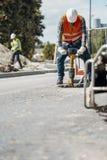Arbeider in helm en weerspiegelend vest met boor asphal herstellen royalty-vrije stock foto